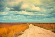 Rural Dirt Road In The Field With Cloudy Sky
