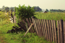 Old Broken Fence Against The Field In A Summer Sunny Day
