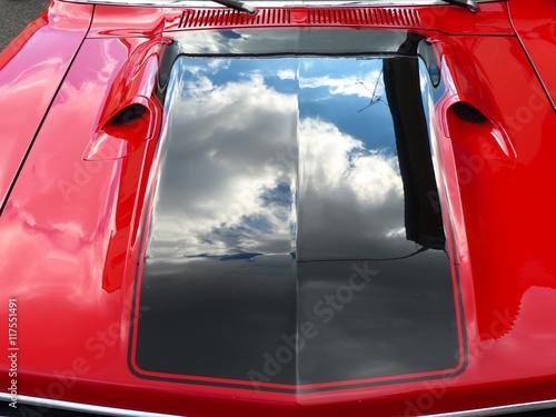 Photo  Dunkle Regenwolken spiegeln sich in der schwarz glänzenden Motorhaube eines rote