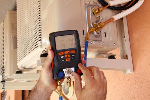 Fotografiet  Instalador verificando el compresor de aire acondicionado