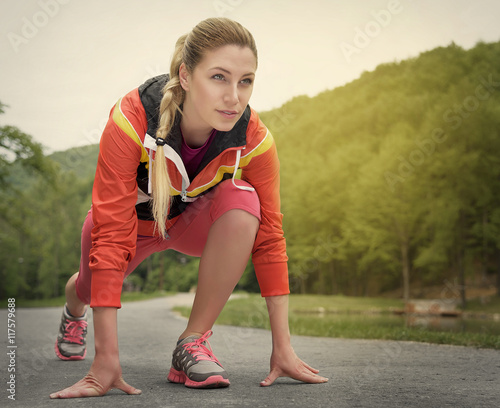 Foto op Aluminium Vruchten Attractive blonde woman running on track outdoors.