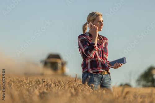 Fotografía Female farmer walking through field checking wheat crop
