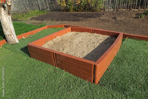 Modern Plastic Sanbox On The Artificial Lawn In Sunny Autumn Garden