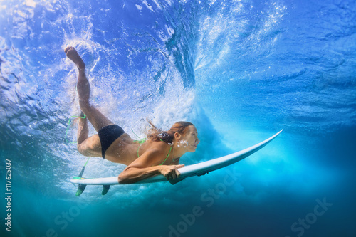 Young active girl in bikini in action - surfer with surf board dive underwater under breaking big ocean wave. Family lifestyle, people water sport adventure camp, beach extreme swim on summer vacation