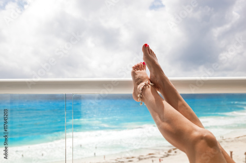 Tanning legs in hotel terrace over sea view Canvas Print