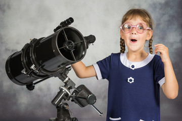 Naklejka Girl astronomer happily surprised by what he saw in the telescope