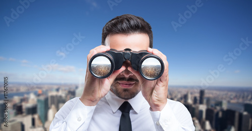 Fotografía  Businessman using binoculars to look at the city