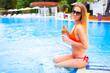 Young pretty blond woman in a orange bikini and sunglasses enjoy