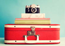 Vintage Film Camera Over Books And Red Suitcase