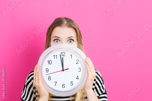 Fotografía  Woman holding clock showing nearly 12
