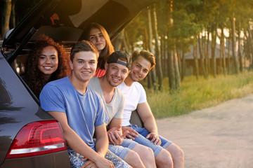 Friends sitting in a car trunk