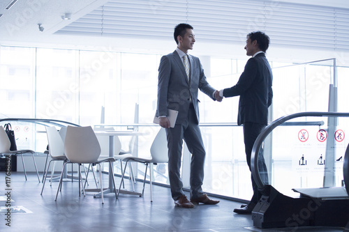 Fotomural Two young businessmen have a handshake in the office building lobby
