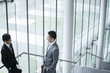 Two businessmen have a stand talking in the lobby of the building