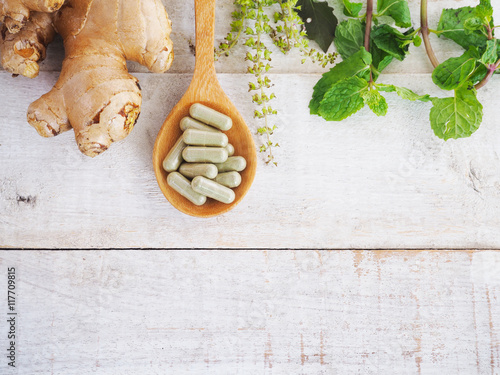 Fotografia  herbal pills on wooden spoon and green herb.