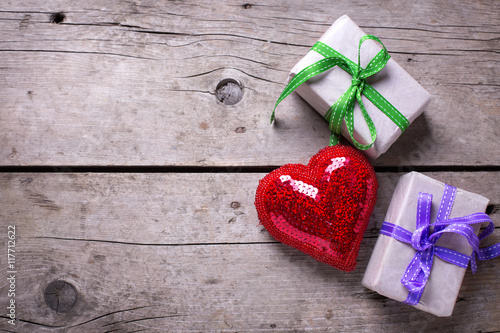Festive gift boxes with presents and red shiny heart on vintage