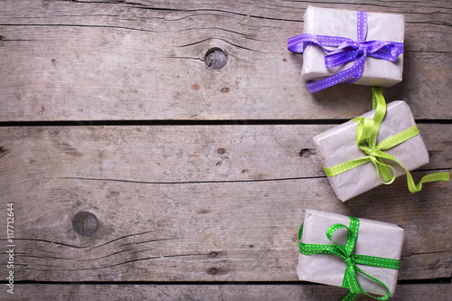 Feestive gift boxes with presents on vintage wooden background.