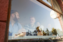 Businessmen Communicating In Cafe Seen Through Glass Window
