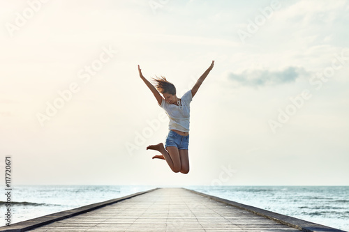 Stampa su Tela Happy jumping girl on the pier