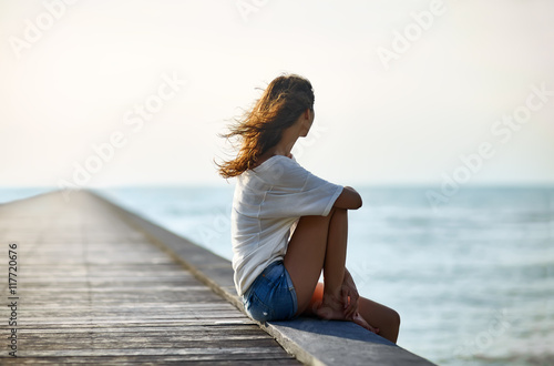 Fotografía  Young beautiful woman sitting on the pier