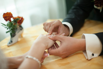 Obraz na płótnie Canvas A closeup of bride's hands lying over the tea table while groom