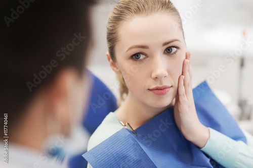 Fotografia  male dentist with woman patient at clinic