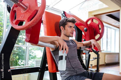 Plakat Portrait of a fitness man resting on bench at gym