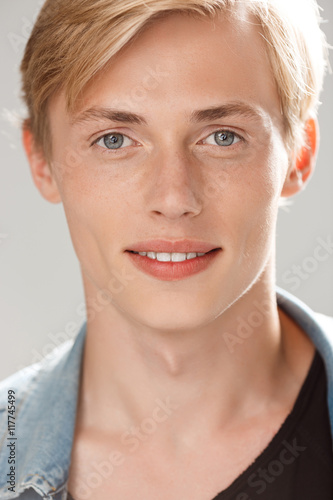 Fototapeta Close up portrait of handsome smiling blond young man wearing casual black t-shirt and jeans jacket looking in camera on grey background obraz na płótnie