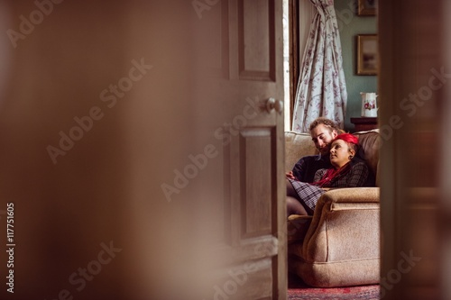 Romantic couple sitting on sofa at home