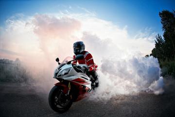 rowerzysta pozostający na drodze rowerowej z dymem opony, wypalony w moto show. zachód słońca