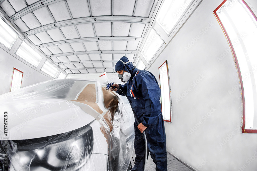 Fototapety, obrazy: worker painting a white car in special garage, wearing costume and protective gear