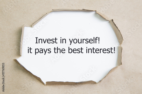 Fotografía  The quote Invest in yourself, it pays the best interest, appearing behind ripped paper
