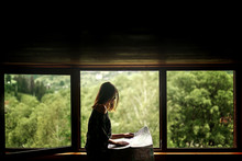 Woman Holding Map Sitting At Window With View At Amazing Mountai