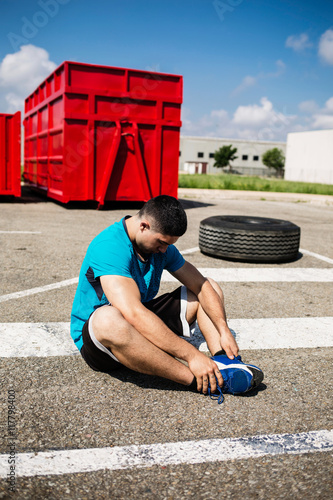 Black-haired sportsman stretching after exercising on road
