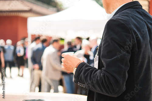 Business man holding a glass of white wine Wallpaper Mural