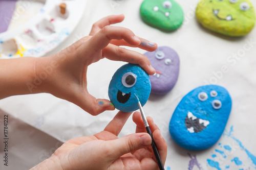 Photo  Child painting a stone for making a monster craft