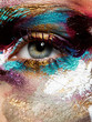 Beauty concept. Perfect artistic, creative makeup. Closeup of beautiful woman's eye with bright glossy colorful makeup. Makeup with a different texture and colors: gold, aquamarine, blue and purple