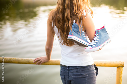 Fotografia, Obraz  Tied pair of sneakers hanging on a girl
