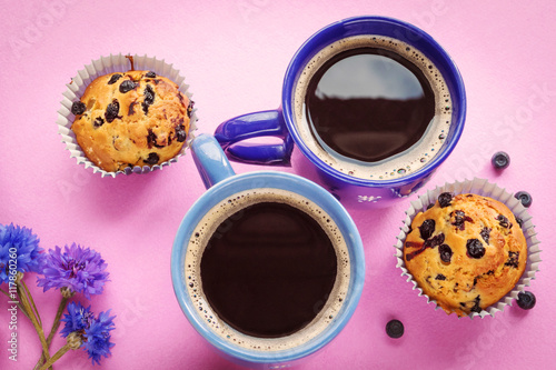 Blueberry muffins, two cups of coffee and cornflowers on pink ba - 117860260