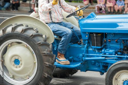 фотография  Vintage blue Ford tractor with big wheels and farmer.