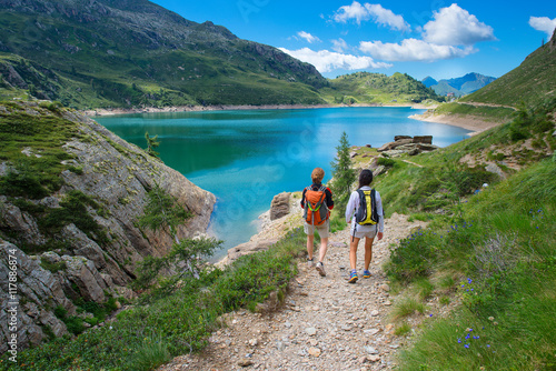 Two friends during a hike in the mountains walking near an alpin Wallpaper Mural