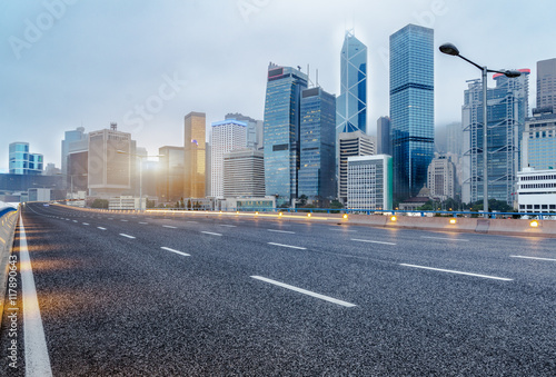 city empty traffic road with cityscape in background - 117890643