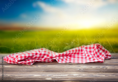 Red picnic cloth on wooden table mature bokeh background.