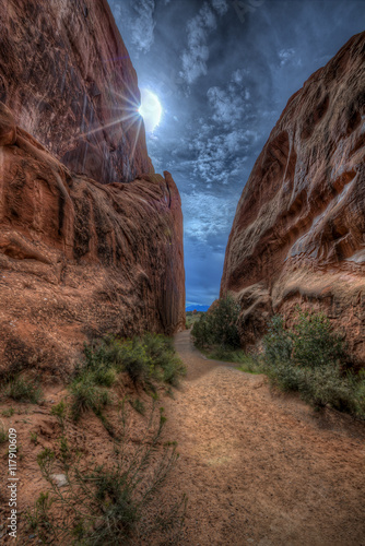 Foto op Aluminium Diepbruine A narrow path through some Red Sandstone Rock, with the sun trying to burn through building storm clouds.