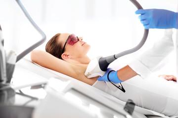 Depilacja laserowa pach. Kobieta na zabiegu depilacji laserowej