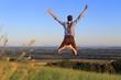 Mann in Tracht springt glücklich über Wiese