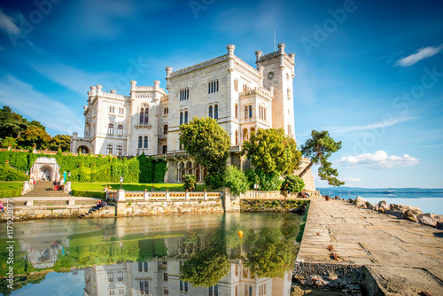 Fotobehang Oude gebouw View on Miramare castle on the gulf of Trieste on northeastern Italy. Long exposure image technic with reflection on the water