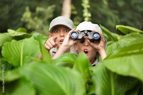 Fotografía  excited young campers hiding in grass looking through binoculars