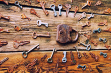 Old Rusty Padlock And Keys On Wooden Background