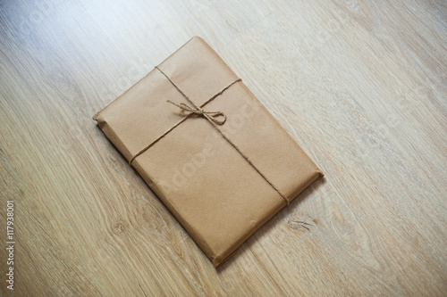 Fotografía  wrapped gift kraft paper on a wooden background