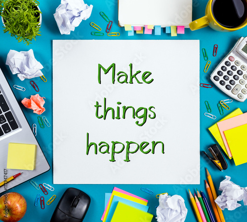 Make things happens. Office table desk with supplies, white blank note pad, cup, pen, pc, crumpled paper, flower on blue background. Top view. © projectio